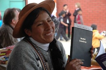 A smiling woman holds a New Testament
